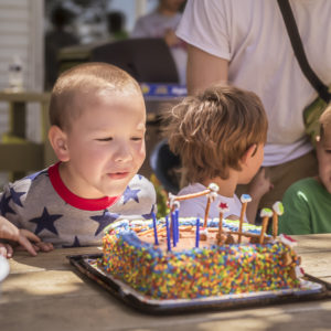 5 year old boy blowing out candles on his birthday cake
